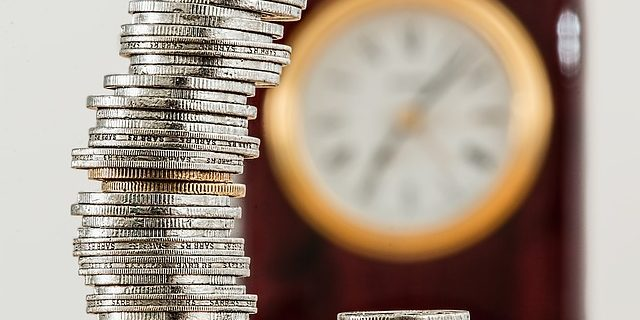 An image of stacks of coins with a clock in the background, representing time spent on a case being a determining factor in evaluating reasonableness of Indiana attorney fee award decisions.