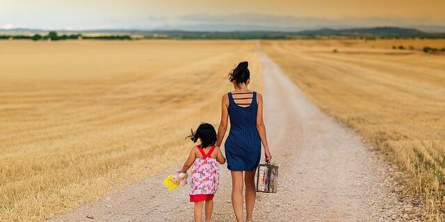 An image of a woman and child walking a path through an open field, representing the impacts of Indiana child custody cases and mental health on families.