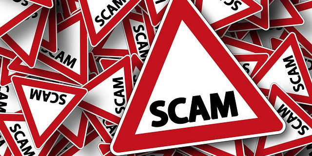 Image of a stack of red and white warning signs with the word scam on each sign, representing tax scams in Indiana. If you have been the victim of a tax scam in Indiana, Camden & Meridew, P.C. can help.