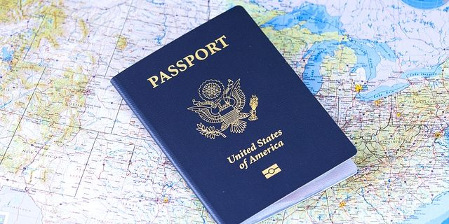 An image of a U.S. passport lying on a U.S. map, representing the potential consequences of delinquent taxes, including IRS passport revocation.