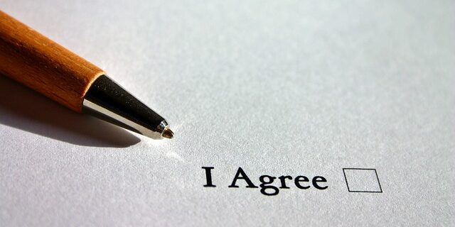 """Image of a pen lying on a piece of paper in the background with the words """"I agree"""" next to a box to be checked off in the foreground; this represents the agreement parties make when they enter into a contract and the willingness to abide by and enforce an arbitration agreement contained in that contract."""