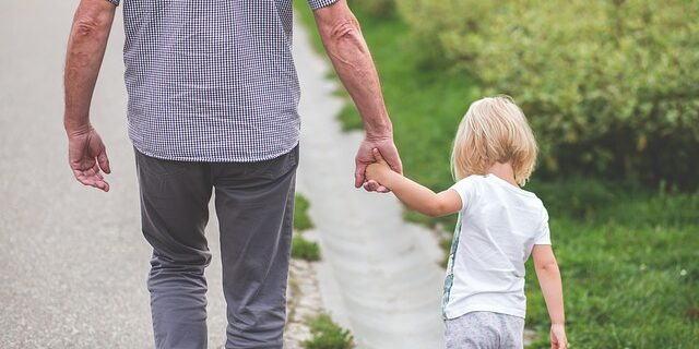 Picture of a child holding hands with a man, representing how Camden & Meridew can help you navigate paternity laws in Indiana.