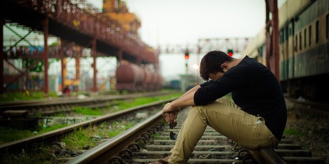 An image of a regretful man sitting on railroad tracks, representing the opportunities available to start fresh after criminal convictions by applying for Indiana expungements.