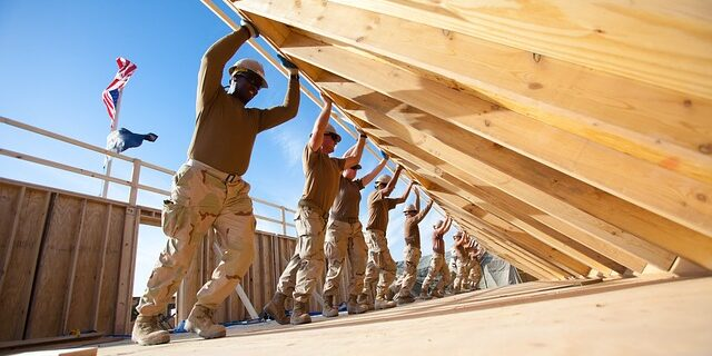 Image of construction workers raising a framed wall for home construction, representing how construction and other labor companies can secure payment for work using an Indiana mechanic's lien.
