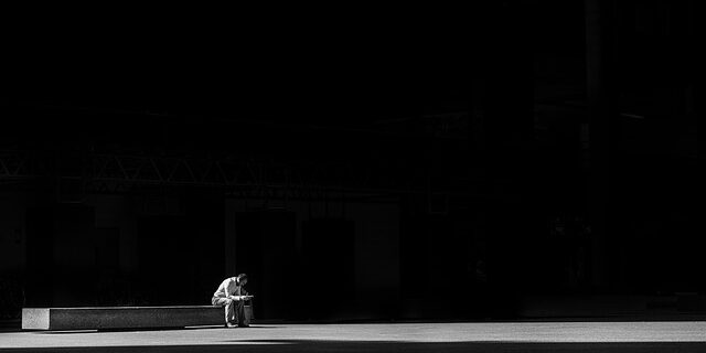 An image of a man sitting alone in stark surroundings, representing how an Indiana Social Security attorney can help ease the burden of enduring the wait time for Social Security in Indiana.