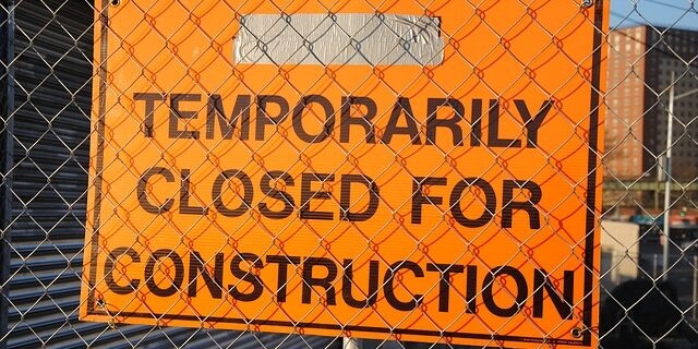 "An image of a sign that reads ""temporarily closed for construction,"" representing the delays that can occur when responsible parties fail at negotiating construction contracts with a focus on dispute prevention and resolution."