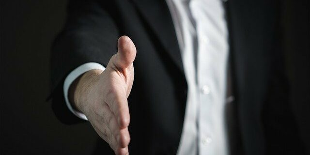 An image of a man reaching out for a handshake, representing the need to enlist an Indiana contract attorney when you don't know if a written contract is needed or have other questions related to the Indiana statute of frauds.