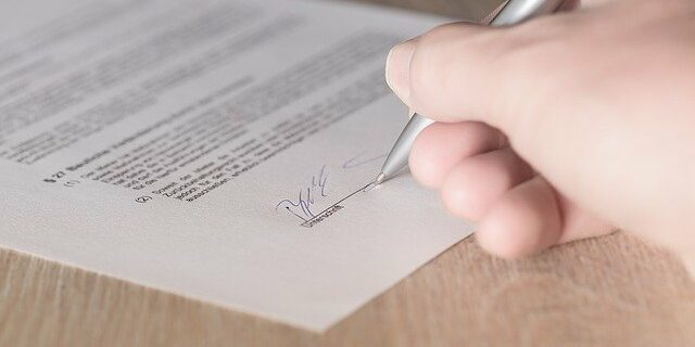 Image of someone signing a contract, demonstrating how an Indiana real estate lawyer from Camden & Meridew, P.C. can help protect your interests through drafting and review of Indiana real estate contracts.