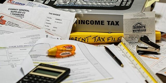 Image of bills, tax books, and a calculator, representing how Indiana tax settlement attorney Julie Camden helps Hoosiers effectively manage their tax debt.