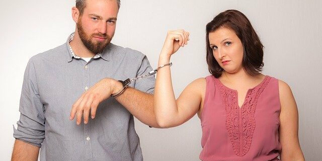 Image of a man and woman, connected together with handcuffs, illustrating how the innocent spouse rule can provide relief to a spouse seeking to escape liability for the other spouse's tax deficiency.