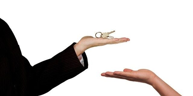 Image of one hand giving house keys to another, representing how working with an Indiana real estate lawyer from Camden & Meridew, P.C. can help you avoid Indiana home sale disputes.