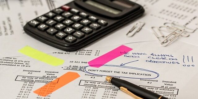 Image of calculator and financial records mentioning tax implications, representing how you can turn to Julie A. Camden at Camden & Meridew for tax lien help in Indiana.
