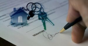 Image of a businessperson signing a contract with a set of keys sitting on it, representing the need for an Indiana real estate lawyer when making residential or commercial real estate transactions or handling disputes.