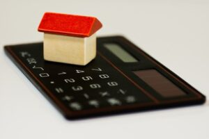 Image of a toy house on a calculator, representing the need for an Indiana foreclosure defense attorney when you are at risk of foreclosure.