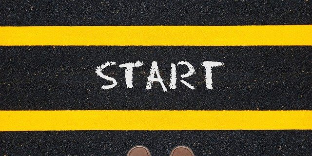 """A pair of feet standing at a yellow line in a road with the word """"start,"""" representing how an Indiana business lawyer at Camden & Meridew can help you with starting a business in Indiana."""
