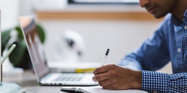 Image of a man with a laptop and notepad, representing the Indiana Business Entity Harmonization Act and how an Indianapolis business attorney from Camden & Meridew can help you navigate them.