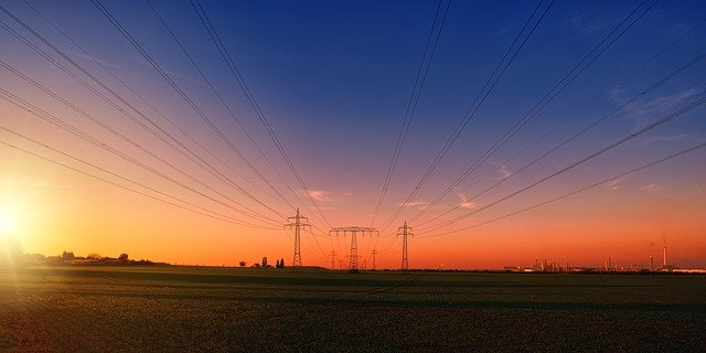 Image of power lines over a field, representing Indiana utility easement laws and how an Indiana utility easement lawyer at Camden & Meridew can help with related legal matters.